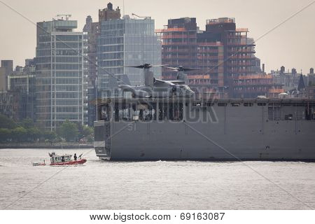 NEW YORK - MAY 27: A US Coast Guard boat runs alongside the stern of the USS Oak Hill (LSD 051) on the Hudson River after departing Pier 92 at the end of Fleet Week NY on May 27, 2014.