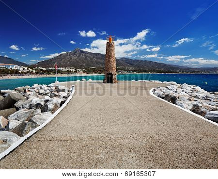 Lighthouse at the end of breakwater in the Puerto Banus in Marbella, Spain
