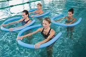 Fitness class doing aqua aerobics with foam rollers in swimming pool at the leisure centre poster