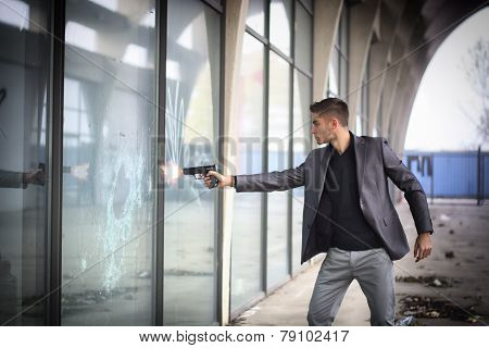 Young detective or policeman or mobster firing a gun to a window glass
