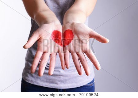 Drawing hart on female hands close-up