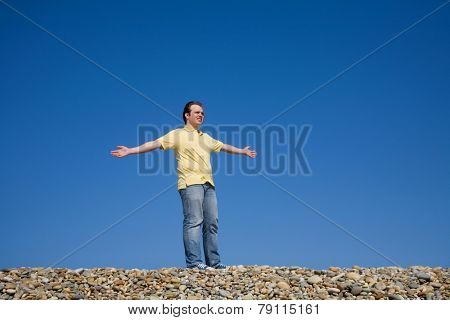 man with arms wide open at the beach