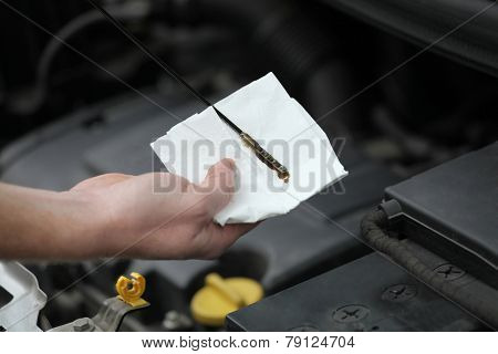 Auto Mechanic Checking Engine Oil Dipstick In Car