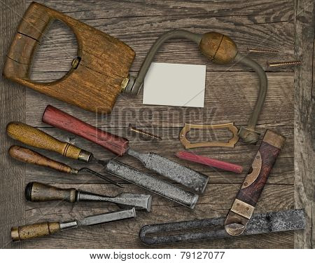 vintage woodworking  tools over wooden bench, blank plate and business card for your text