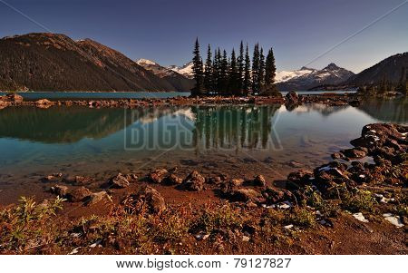 Interesting evergreen trees in a clear mountain lake