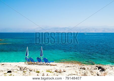 Sunbeds And Umbrellas (parasols) On A Rocky Beach In Corfu Island, Greece.