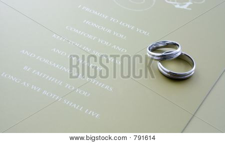 A pair of wedding rings with wedding vows poster