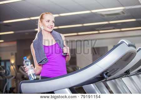 Attractive young woman after running on a treadmill exercise at the fitness club