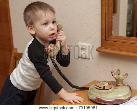Two years old white boy calling on the old-fashioned onyx stone phone indoors. Telephone is on the wooden table in the room. poster