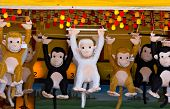 Prize monkeys at a game of chance on a seaside boardwalk. poster