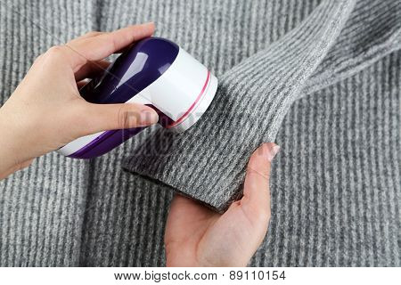 Female hands with Wool shaver on wool sweater background poster