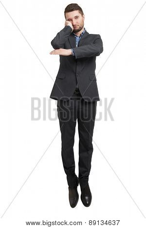 tired businessman hanging in the air and looking at camera. isolated on white background