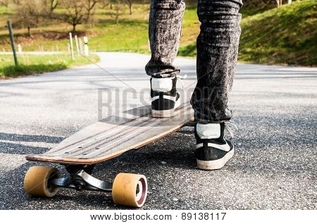 Shoes and legs of a young boy in black jeans on a longboard on a rural street