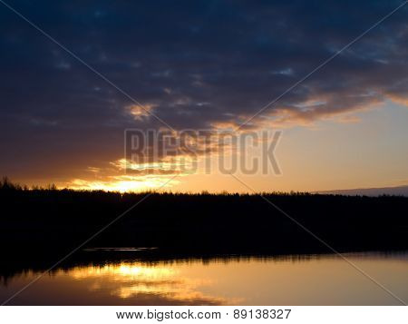 Sun rises over the forest lake