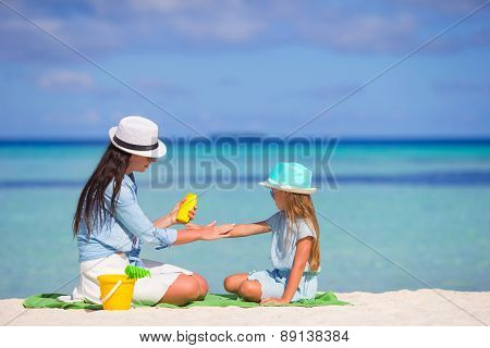 Young mother applying sun cream on her kid poster