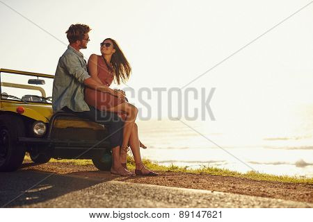 Young couple looking into each other's eyes. Romantic young couple sitting on hood of their car enjoying the moment outdoors with copy space. Young couple in love on a road trip. poster