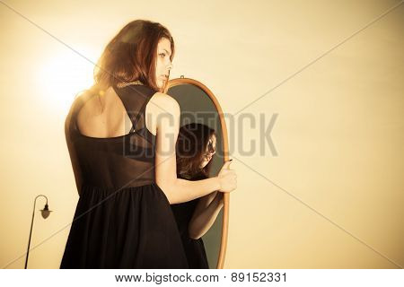 Thoughtful Woman Looks At Reflection In Mirror
