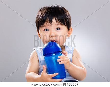 Baby boy learn to use water bottle for drinking