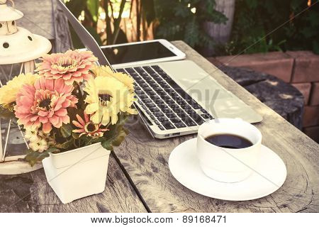 A Cup Of Coffee And Laptop On Wood Floor With Flower