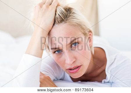 Thoughtful blonde woman lying on the bed in her bedroom