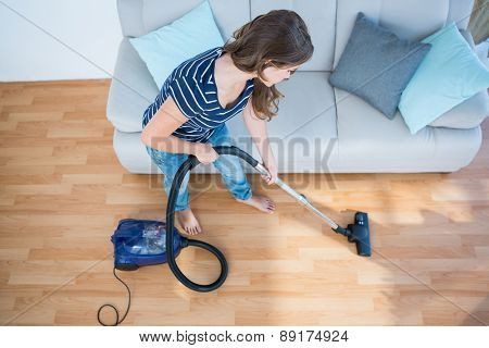 Woman using vacuum cleaner on wooden floor at home in the living room