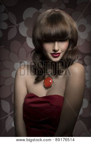 Pretty mysterious gorgeous woman with smooth brown hair with straight fringe wearing red satin top big old necklace and red lipstick her eyes are in shadow. poster