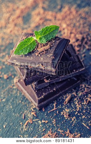Chocolate. Black chocolate. A few cubes of black chocolate with mint leaves.