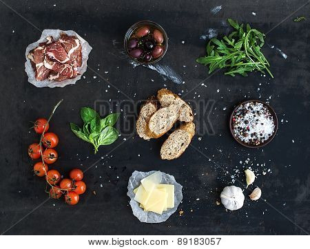 Ingredients for sandwich with smoked meat, baguette, basil, arugula, olives, cherry-tomatoes, parmes