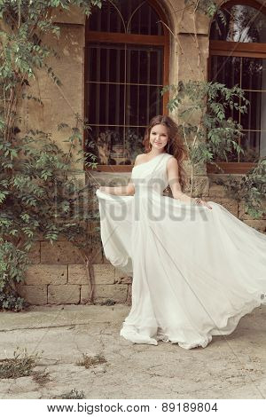 Beautiful Young Bride Girl In Wedding Dress With Blowing Chiffon Skirt. Outdoor Portrait. Soft Color