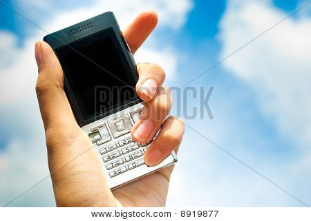 Mobile phone in hand over blue sky background.
