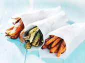 trio of carrot, zucchini, and sweet potato fries wrapped up in wax paper cones poster