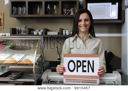 Happy Owner Of A Café Showing Open Sign