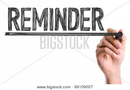 Hand with marker writing the word Reminder