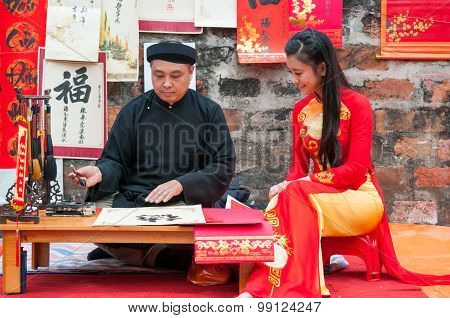 Old master write ancient letters for a girl in Aodai costume