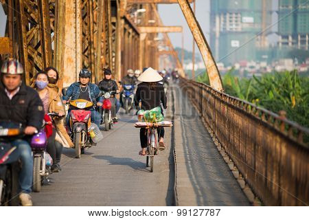 People ride motorbike in Long Bien bridge in Hanoi, Vietnam.