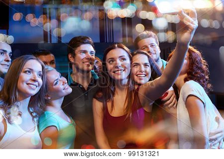 party, technology, nightlife and people concept - smiling friends with smartphone taking selfie in club