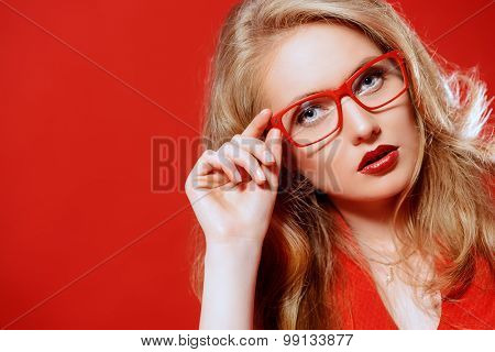 Beautiful young woman with magnificent blonde hair wearing red dress and elegant red glasses. Beauty, fashion. Optics, eyewear. Red background. poster