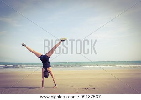 Fit woman cartwheeling on the sand at the beach
