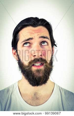 Handsome hipster thinking and looking up on vignette background