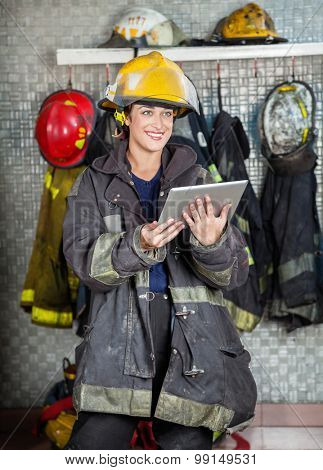 Smiling firewoman in uniform looking away while holding digital tablet at fire station