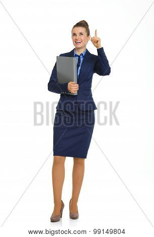 Smiling Businesswoman Holding File And Pointing Upwards