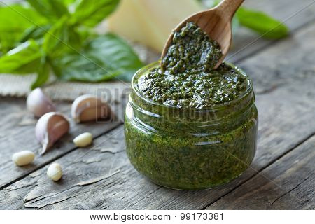 Traditional Italian pesto vegetarian food with basil nuts and olive oil. Wooden spoon gaining portion of sauce. Vintage wooden table background. Rustic style and natural light. poster