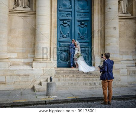 Wedding couple being photographed in front of a church in Paris