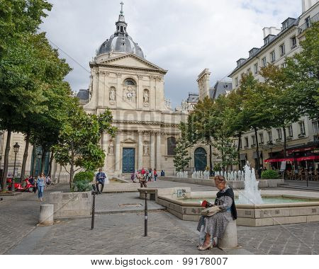Woman sitting reading a book in a plaza