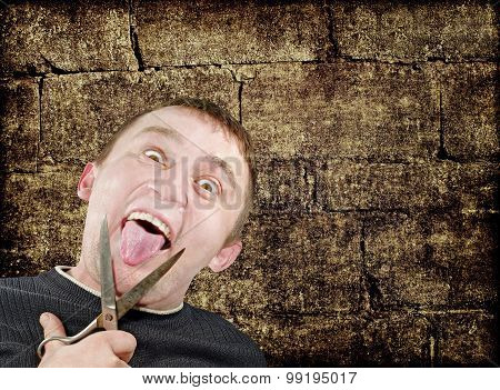 Mad Man With Scissors Cuts Off Itself Tongue On Grunge Background.