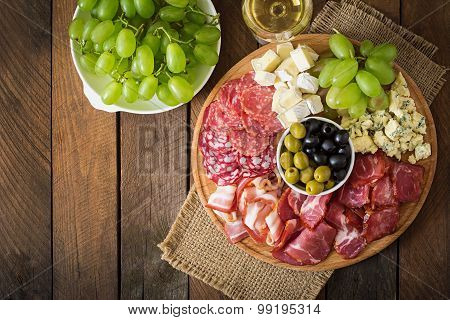 Antipasto catering platter with bacon, jerky, salami, cheese and grapes on a wooden background