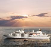 Small luxury cruise ship leaving port at sunset poster