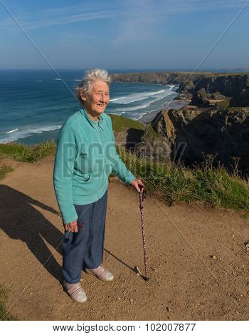 Old lady standing with walking stick by beautiful coast scene