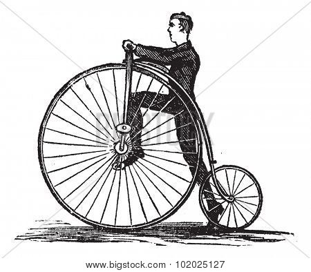 Penny-farthing or High Wheel Bicycle, showing how to mount the bicycle by stepping on the pedal, vintage engraved illustration. Trousset encyclopedia (1886 - 1891).