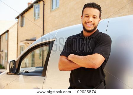 Portrait of mixed race tradesman by a van